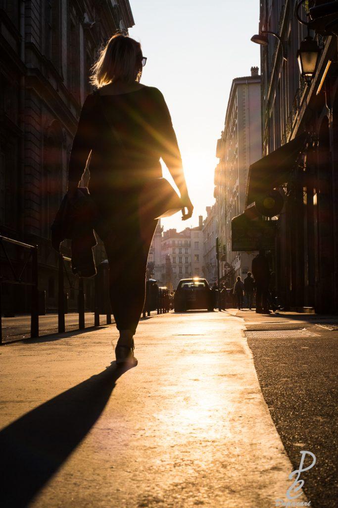 photo en contre jour une passante marchant vers le soleil tout est dorée hotel de ville Lyon