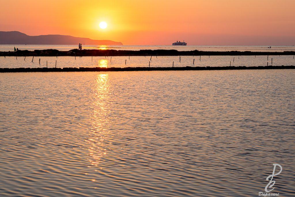 Coucher de soleil à Nubia en Sicile mer 2/3 de l'image avec bateau au fond et personnage marchant à gauche couleur orangé objectif 56mm