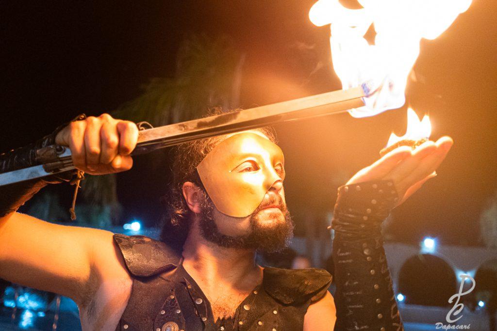 spectacle de feu en main et torche dans l'autre main personnage très rapproché regard en direction de la droite vers sa main