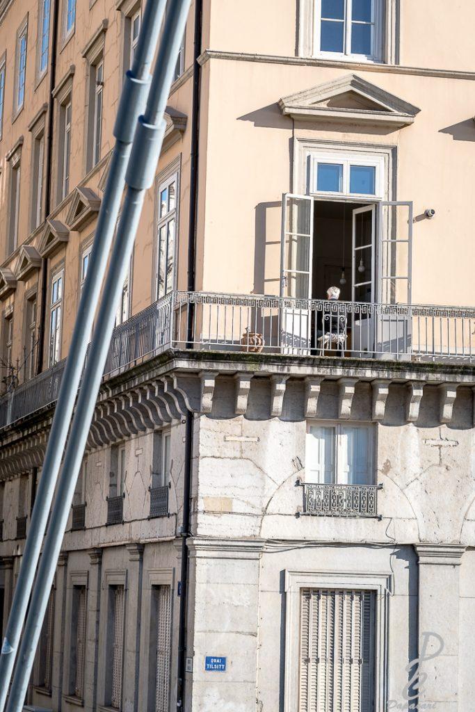 cadrage serrer d'un batiment depuis la passerelle saint george un personne est assis dos à la fenêtre entrain de regarder la télé
