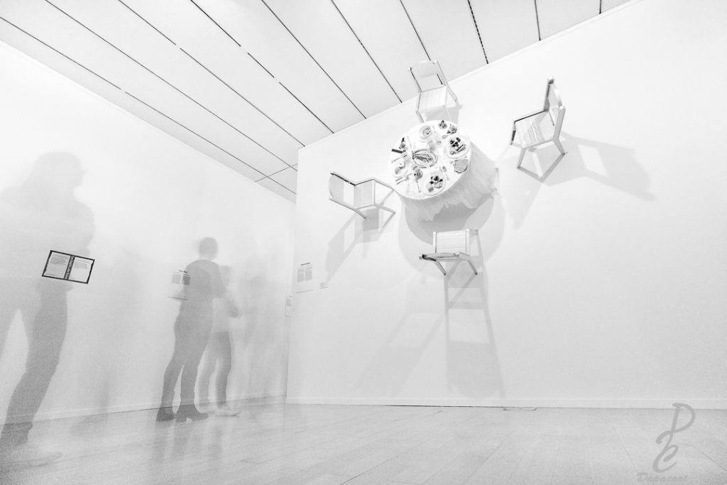 pose longue dans musée art comptemporain table sur le mur, personnage transparent. Photographier dans les musée astuce